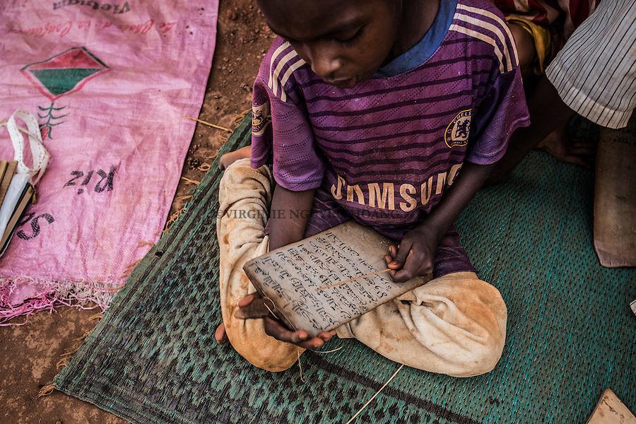 CAR, Yelloke: A young boy is reading arabic on a wood tablet in his town in Yelloke. After the crisis in CAR, the anti-balaka of Yelloke city have decided to build a village where the muslim minority, the Peuls, can live and be protected by the UN.  23th April 2016. <br /> <br /> RCA, Yelloke: un jeune gar&ccedil;on lit de l'arabe sur une tablette en bois dans son village &agrave; Yelloke. Apr&egrave;s la crise de Centrafrique, les anti-balaka ont d&eacute;cid&quot; de construire un village pour la minorit&eacute; musulmane, les peuls, o&ugrave; ils peuvent vivre et &ecirc;tre prot&eacute;g&eacute;s par l'UN.  23 avril 2016.