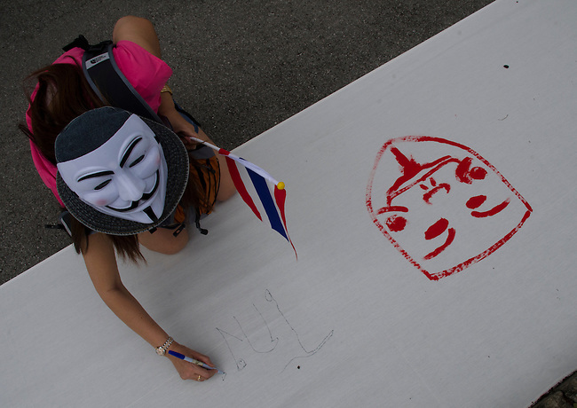 BANGKOK, July 14: Protestor writes on a banner to display to the public as anti-government protestors supporting the white-mask movement against corruption in the Yingluck Shinawatra government gathered at Lumpini Park on the second anniversary of the Yingluck administration to protest the blatant corruption in government policy and practice. July 14, 2013, Bangkok, Thailand