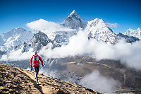 A trail runner starting up the first pass, Kongma La, above Chukhung while starting the 3 Passes tour, with a view of Ama Dablam in the background. Khumbu Valley, Nepal.