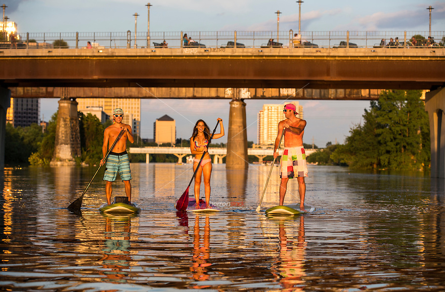 A group of friends navigate Lady Bird Lake in Austin, Texas, the Stand Up Paddle (SUP) Capital of the world, on a beautiful summer's day.