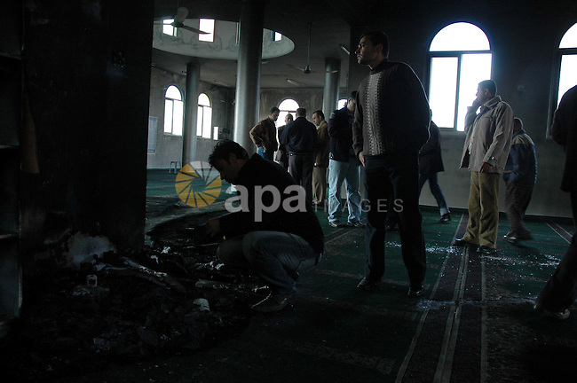 Palestinians inspect the damage to a mosque that was set on fire in the West Bank village of Kfar Yasuf, south of the West Bank city of Nablus, on December 11, 2009. Jewish settlers are suspected in the attack on the mosque where fire was set to a library and hate messages were sprayed on the building, Palestinian security sources said. Photo by Nedal Shtieh