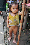 A young girl walks in the dirty street with minimal clothing and no shoes. <br />