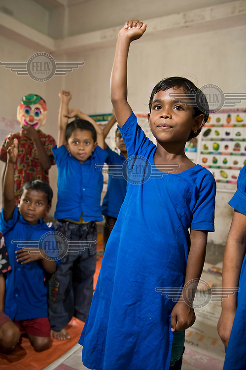 A girl raises her hand in class at a school in Patuakhali district.