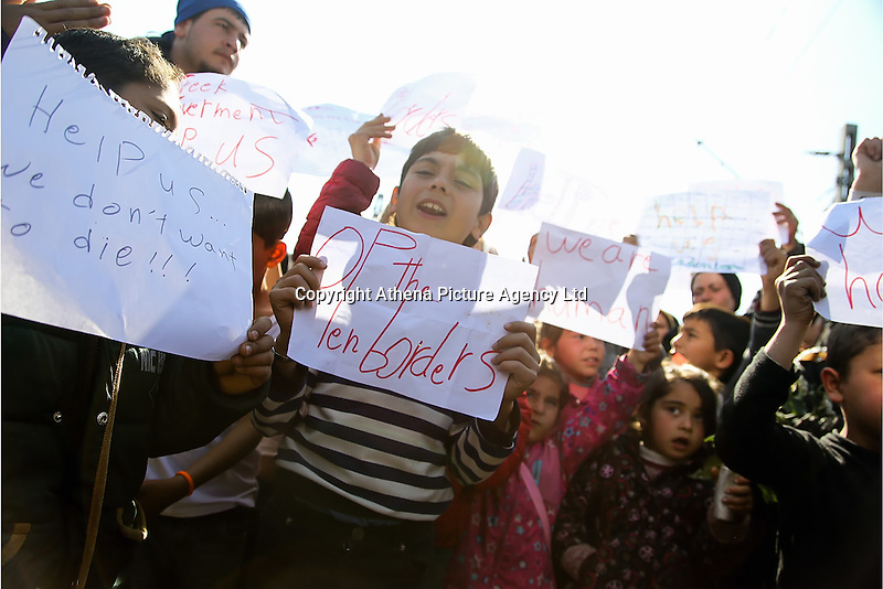 """Pictured: Children holding pieces of paper with """"Open Borders"""" slogans Thursday 03 March 2016<br /> Re: Migrants have closed off the railway track at the Greek Fyro Macedonian border in Idomeni, Greece,"""