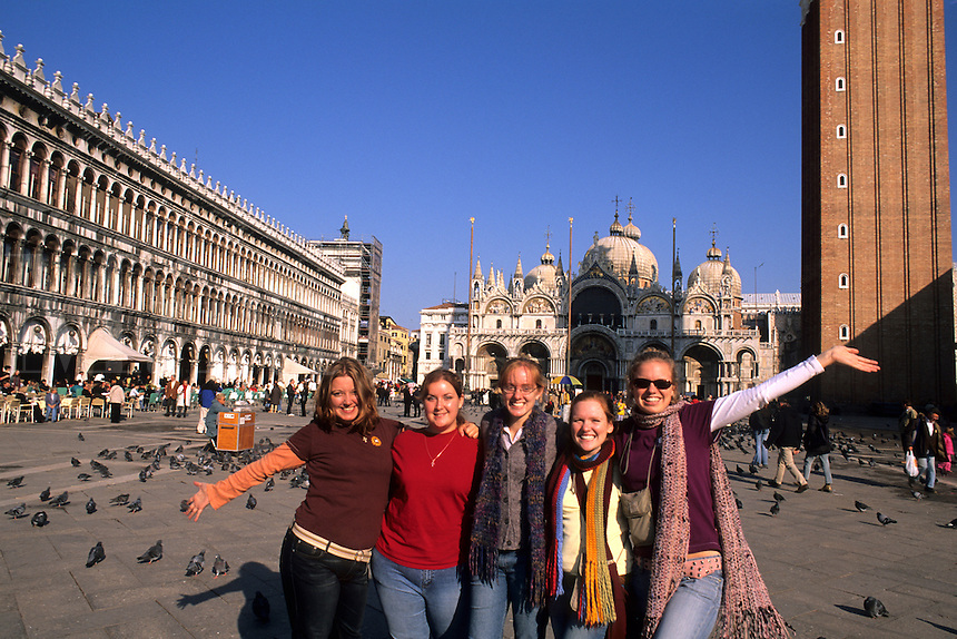 Group of colege girl tourists brightly dressed in front of the Famous St Marks Church in San Marcos Plaza in romantic Venice Ital