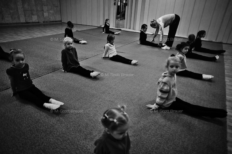 Trainer Elena Orlova helps girls age 4 and 5 stretch during rhythmic gymnastics training at the Dinamo Sports Palace in Moscow, Russia. The girls have been training for about 3 months.