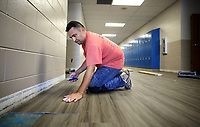 NWA Democrat-Gazette/DAVID GOTTSCHALK  Wilfredo Calderon, with Davis Flooring, fits a piece of LVT tile Friday, July 6, 2018, in the hallway at Woodland Junior High in Fayetteville. New tile is being put down new tile in the hallways and cafeteria of the school. Northwest Arkansas school districts are busy working on facility improvement projects while staff and students are away for the summer break.