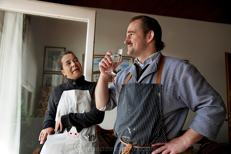 After hours of work and a breakfast of pretzel bread, sausage, and coffee, Markus and his wife, Sonja, discuss the day's plans for their catering business at their home in Endingen, near Freiburg im Breisgau, Germany.  (From the book What I Eat: Around the World in 80 Diets.) The caloric value of his typical day's worth of food in March was 4600 kcals. He is 43 years of age; 5 feet, 9 inches tall; and 160 pounds.  Germans are among the biggest meat eaters in Europe, but eat slightly less meat than in decades past.  MODEL RELEASED.