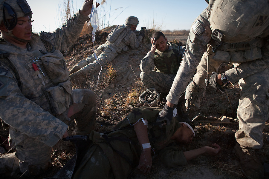 A wounded civilian - struck in the head by shrapnel from an Taliban RPG fired at troopers from Charlie Co. 1st Battalion 12th Infantry Regiment, 4th Infantry Division in Zhari District, Kandahar, Afghanistan - waits to be medevaced by air after it became apparent that he had received a significant concussion and was periodically on the verge of  losing consciousness. The violently contested district sits astride the strategically Highway 1 ringroad between Kandahar and Lashkar Gah and is seen by some as the birthplace of the Taliban movement.