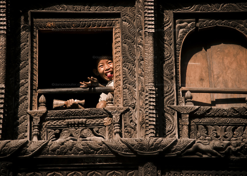 A schoolboy at an ornately carved school window in the Annapurna region of the Nepal Himalaya. Nepal April 1995