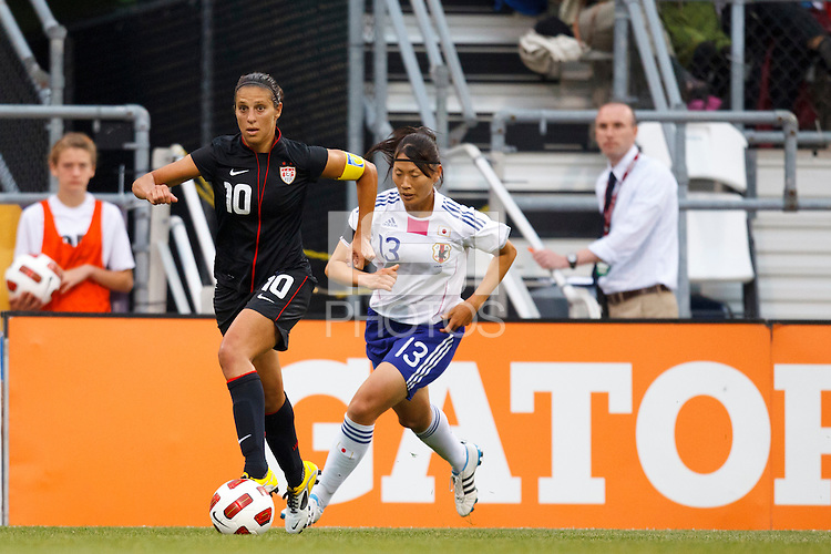 14 MAY 2011: USA Women's National Team midfielder Carli Lloyd (10) dribbles the ball by Japan National team Rumi Utsugi during the International Friendly soccer match between Japan WNT vs USA WNT at Crew Stadium in Columbus, Ohio.