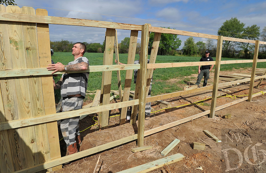 NWA Democrat-Gazette/MICHAEL WOODS &bull; @NWAMICHAELW<br /> Drew Rosser, (far right) with the Benton County Sheriff's office, watches as Benton County Jail inmate Donald Ames (left) and other inmates work on building a new fence Friday April 15, 2016  for the impound lot at the Pea Ridge Police Department.   Inmate work details are used to help with a variety of different projects for local small cities.