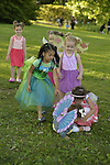 Old Westbury, New York, U.S. - June 21, 2014 - When 15-month-old toddler JASMINE DELGADO. wearing blue fairy wings, fell, help came - her sister JULIA DELGADO in peach dress; 4 1/2 year old triplets: ARIELLE KIRCHHOFER in orange dress, CRISTINA KIRCHHOFER in pink dress, BRIANNA KIRCHHOFER in purple dress; and PRISCILA BLANCHET, 4 years old, in green fairy costume. The six girls, best friends from Bayside, Queens, came with their families to see the Lori Belilove & The Isadora Duncan Dance Company dance throughout the gardens during the Midsummer Night event at the Long Island Gold Coast estate of Old Westbury Gardens on the first day of summer, the summer solstice.