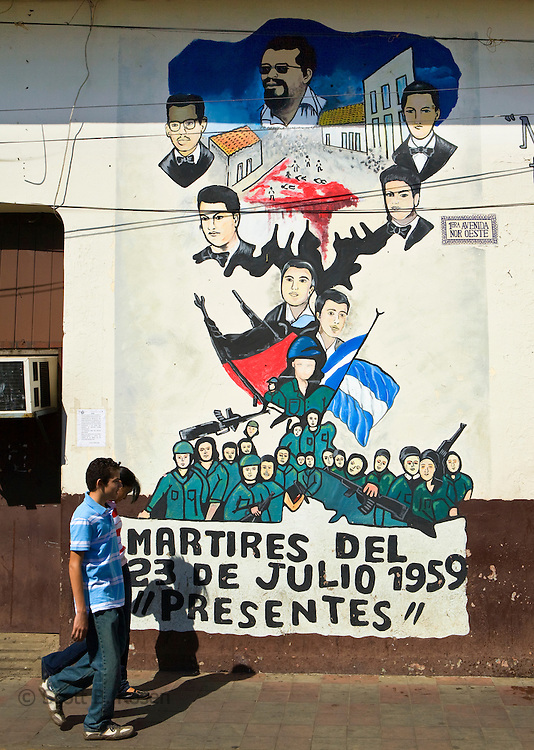 Local Nicaraguan youth walk by Sandinista murals on Avenida Sur Oeste, Leon, Nicaragua