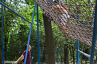 Children climb on a cargo net rope course in Changle Park in Xian, Shaanxi, China.