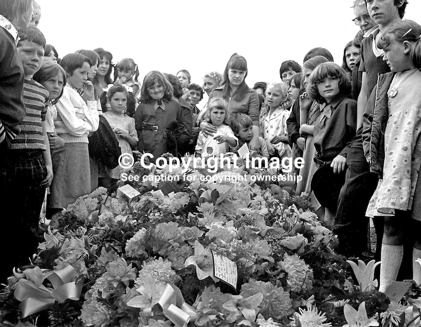 Mourners view the floral tributes at the grave of the three Maguire children, Joanne, 8 years, John, 2 years, and Andrew, 6 weeks, who died as a result of one of the most tragic and horrific incidents of the N Ireland Troubles on 10th August 1976. A car driven by Daniel Lennon, aka Danny Lennon, member, Provisional IRA, mounted the pavement and ploughed into the Maguire family. Lennon died at the wheel having been shot by British soldiers in hot pursuit. The incident gave rise to the birth of the Peace People organisation led by Mairead Corrigan, aunt of the dead children, and another local woman,Betty Williams. 197608130371e.<br />