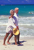 An attractive, fit senior couple walk along Kailua beach on Oahu's windward side.