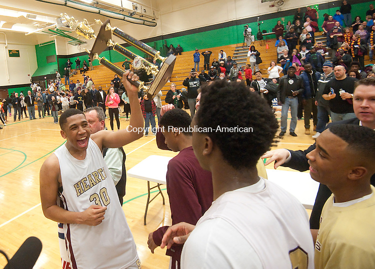 WATERBURY,  CT-030415JS04- Sacred Heart's Isaiah Rascoe (30) hoists the championship trophy following their 68-66 win over Crosby in the NVL Tournament championship game Wednesday at Wilby High School in Waterbury. <br /> Jim Shannon Republican-American