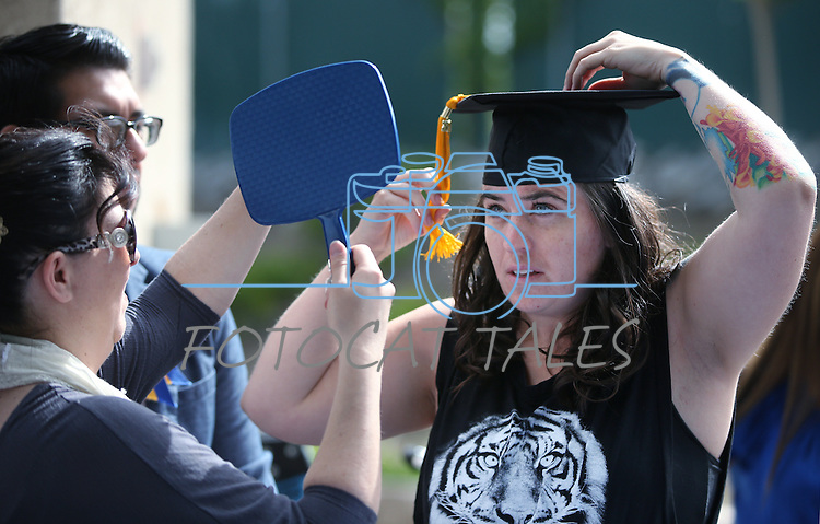 Shannon Segale and Sergio Arteaga help graduate Lynette Carlson get ready before the Western Nevada College commencement at the Pony Express Pavilion, in Carson City, Nev., on Monday, May 19, 2014. <br /> Photo by Cathleen Allison/Nevada Photo Source