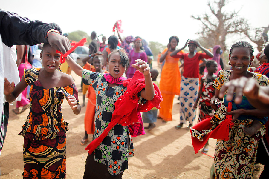 Villagers from Mbakar wear read ribbons on head making a statement that they would not vote for Wade unless electricity was brought into their town. Mr. Wade stopped to hear the petition from the townspeople. At the same time Wade's people got out of their cars to take off as many ribbons as possible from the villagers, and tear down the red flags they had placed on trees. Left side of photo a man takes red ribbon from the girls head. Mbakar, Louga region, Senegal. February 9, 2012. Gabriela Barnuevo