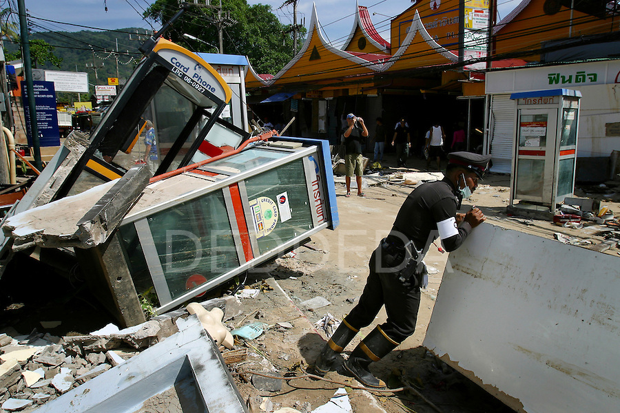 A Thai policeman moves debris in streets next to knocked-over telephone booths where vehicles and various objects were swept away with the tidal waves that hit Patong Beach on Phuket Island, Thailand. On December 26, 2004, a major earthquake generated tsunamis that ravaged coastlines from Southeast Asia to Africa. Approximately 275,000 people were killed and tens of thousands were left homeless, making it one of the deadliest natural disasters in modern history. .