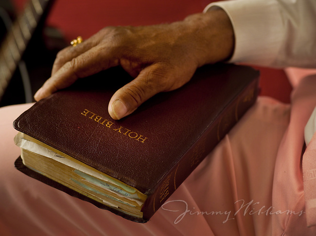 A man holds a bible on his lap while in church