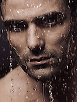 Man face wet from water pouring on it, artistic dramatic portrait.