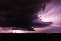 Supercell thunderstorm against a purple sky illumintaed by lightning in Kansas, May 10, 2014