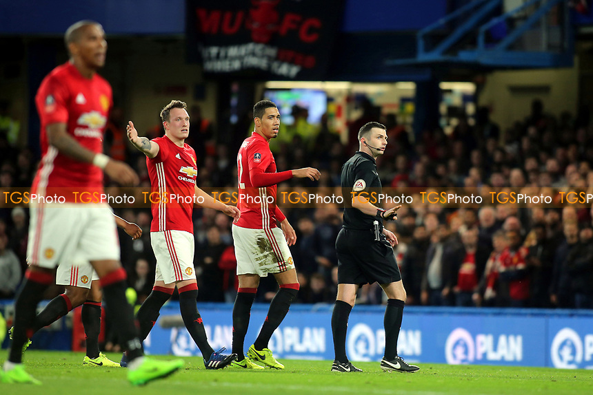 Referee Michael Oliver, looks towards the Assistant Referee after a Chelsea challenge on Manchester United goalkeeper, David De Gea during Chelsea vs Manchester United, Emirates FA Cup Football at Stamford Bridge on 13th March 2017