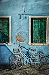 A bicycle leaning against a wall on the colourful island of Burano in Venice, Italy.