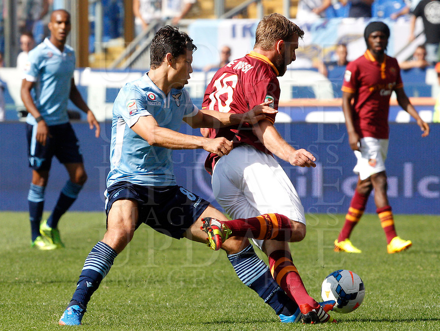 Calcio, Serie A: Roma vs Lazio. Roma, stadio Olimpico, 22 settembre 2013.<br /> AS Roma midfielder Daniele De Rossi, right, is fouled, byLazio midfielders Hernanes, of Brazil during the Italian Serie A football match between AS Roma and Lazio, at Rome's Olympic stadium, 22 September 2013.<br /> UPDATE IMAGES PRESS/Riccardo De Luca