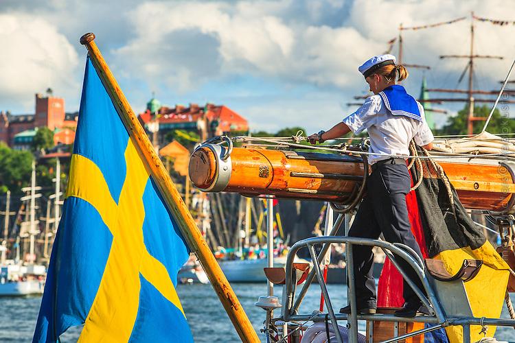 Kvinnlig matros viker segel vid Skeppsbron i Gamla stan i Stockholm