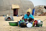 A woman washes dishes in front of her family's tent in Timbuktu, a city in northern Mali which was seized by Islamist fighters in 2012 and then liberated by French and Malian soldiers in early 2013. This woman belongs to the Bella ethnic group, which has traditionally been exploited by the region's lighter-skinned groups.