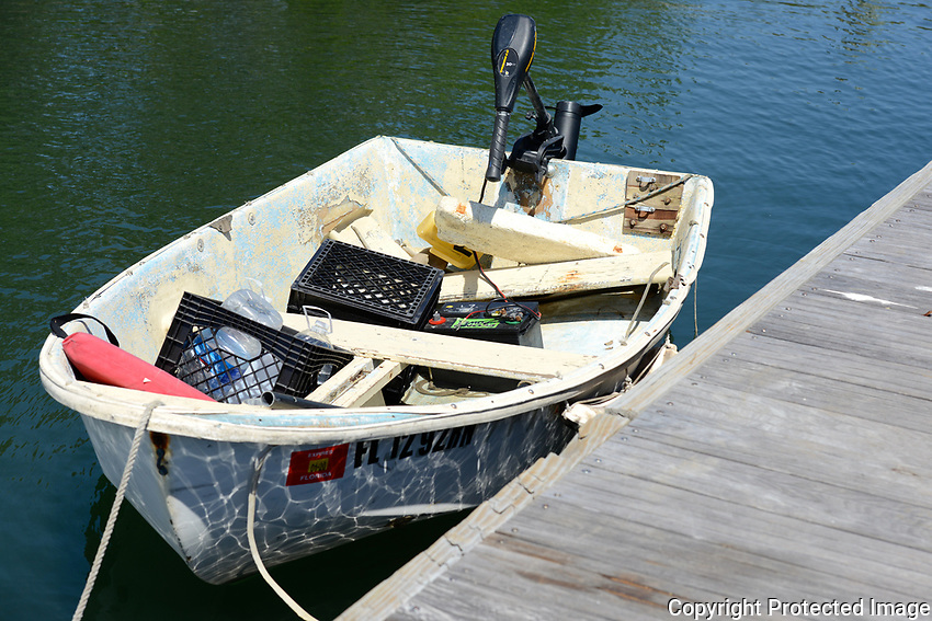 A dinghy that has seen better days is tied up at a dock on the intracoastal waterway near Boynton Beach, Florida.