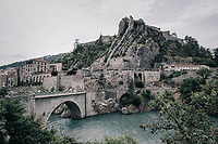 riders riding through the town of Sisteron with it's distinctive monumental rock formations<br /> <br /> 104th Tour de France 2017<br /> Stage 19 - Embrun &rsaquo; Salon-de-Provence (220km)