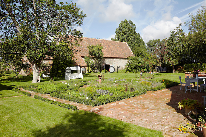 A huge barn is situated at one end of the large garden which is dotted with mature trees