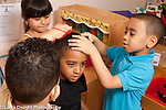 Education preschool 4-5 year olds pretend play group of boys and girls playing hairdresser or barber shop cutting and styling hair of classmates horizontal