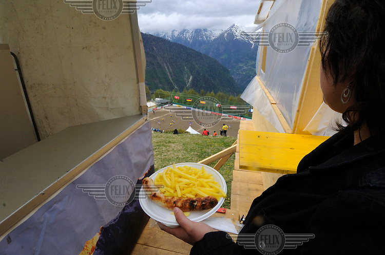 Food break of bratwurst and fries for a supporter at the other official Euro 2008 football tournament: the European Championship of Mountain Villages. The tournament was held at the summer training ground of hosts FC Gspon, standing at 2008 metres above sea-level,  and surrounded by 4000 metre alpine peaks. It is the highest football pitch in Europe, and reachable only by cable car, or a long walk. Amateur league teams from eight countries took part.