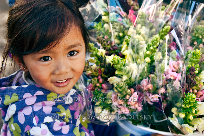 Young girl holding bucket of fresh picked garden flowers, San Luis Obispo on the Central Coast, California