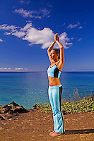A young woman performs yoga with the turquoise water of Makena, Maui behind her.
