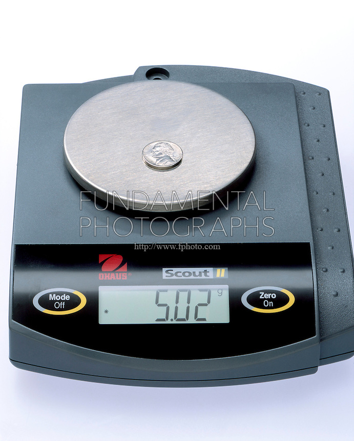 NICKEL ON A BALANCE<br /> A Nickel Has A Mass Of About 5 Grams.<br /> The digital display on the balance shows the weight in grams of the item on the scale.