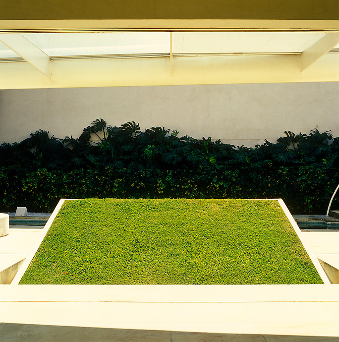 A raised bank of turf on a slope overlooks the swimming pool in the enclosed courtyard