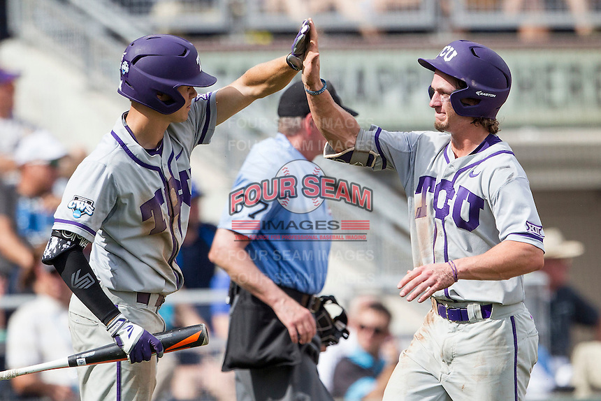 TCU Horned Frogs outfielder Cody Jones (1) is greeted by teammate Connor Wanhanen (16) after scoring against the LSU Tigers in the NCAA College World Series on June 14, 2015 at TD Ameritrade Park in Omaha, Nebraska. TCU defeated LSU 10-3. (Andrew Woolley/Four Seam Images)