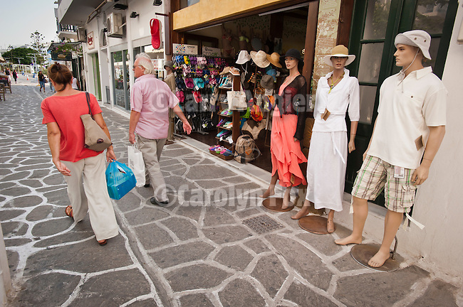 SHoppers with bags walk the narrow streets pasts a shop with mannequin, Naoussa, Paros, Cyclades, Greece