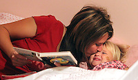 Heather Jacobs kisses her daughter, Ella, 3, while reading bedtime books with her in their Polk City home.  Bedtime is cherished by Heather, as it is about the only time in the day where she will get one-on-one time with each of her children. Heather lost her husband, Eric, in a plane crash in 2006 when she was eight months pregnant with their youngest, Ella, and has since been raising her five young children on her own.