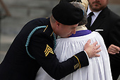 Son of late Arizona Republican Senator John McCain, Jimmy McCain hugs a clergy member after a funeral service at the National Cathedral in Washington, DC on September 1, 2018. Credit: Alex Edelman / CNP