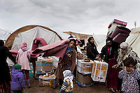 Syrian women and children collect winter blankets and heaters being distributed by the UNHCR in the Domiz refugee camp. 81,000 Kurds from Syria have fled the civil war in their home country and taken refuge in northern Iraq.