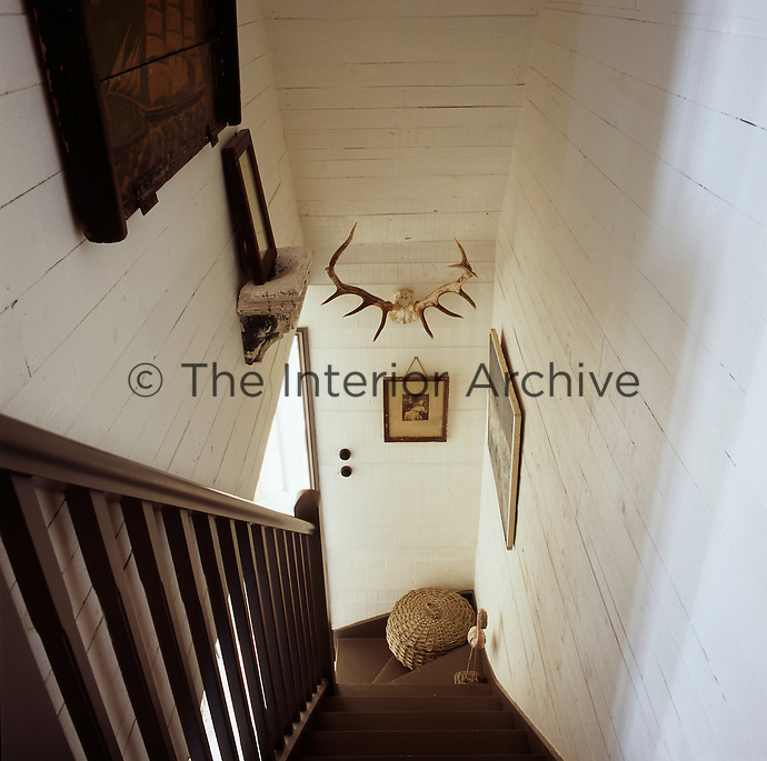 A view down a flight of stairs with a wooden banister and spindles. The timber clad walls have been painted white.