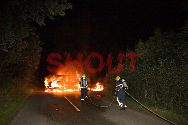 Van well alight being extinguished by firefighters wearing BA Warwickshire UK. This image may only be used to portray the subject in a positive manner..©shoutpictures.com..john@shoutpictures.com