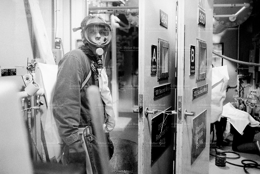 Usa. Utah. Tooele county. Deseret chemical depot. Two workers with gas masks work in a light contaminated area. Tooele chemical agent disposal facility (TOCDF). Program for destruction of chemical weapons and agent. Deseret chemical depot is distant 100 km from Salt Lake City. The Deseret Chemical Depot is one of eight Army installations in the U.S. that currently store chemical weapons. The weapons originally stored at the depot consisted of various munitions and ton containers, containing GB and VX nerve agents or H, HD, and HT blister agent. The Tooele Chemical Agent Disposal Facility is designed for the sole purpose of destroying the chemical weapons stockpile located at the depot. © 1998 Didier Ruef